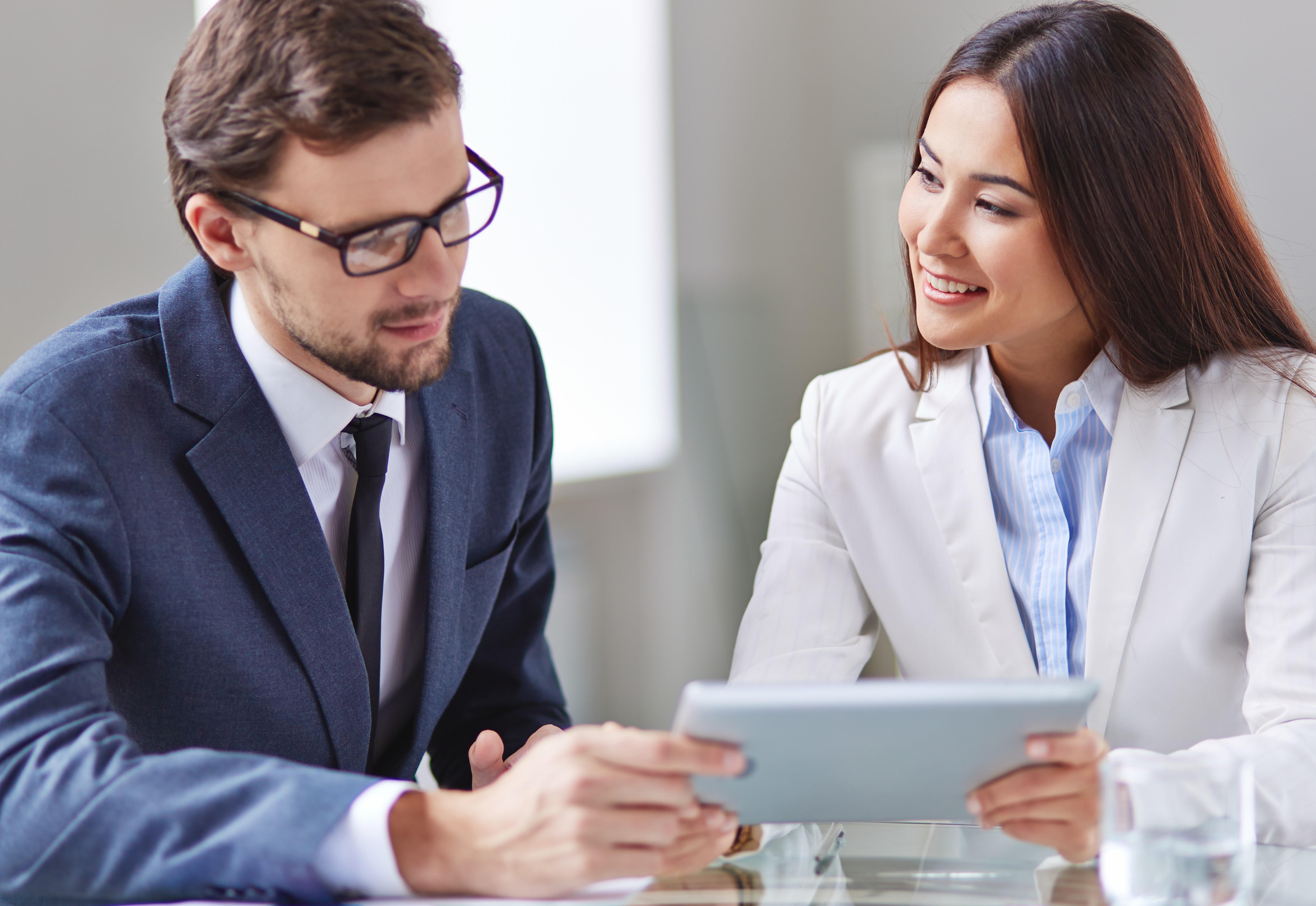 Um homem e uma mulher de negócios fazendo networking em um escritório