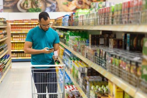Homem no super mercado com aplicativo para entender a importância da gestão da logística no trade marketing