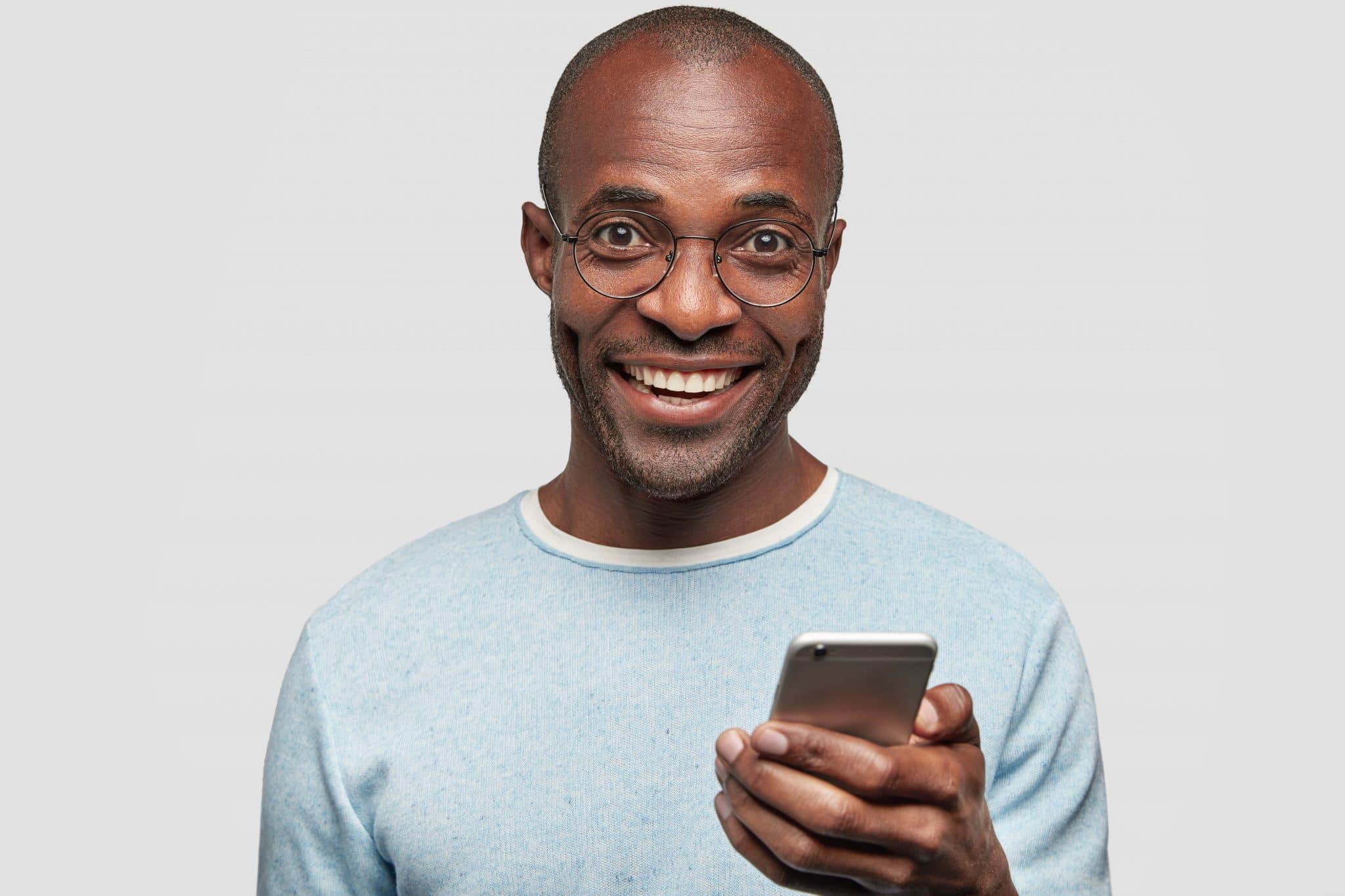 Homem sorrindo com celular na mão que contém seu aplicativo de gestão de vendedores externos