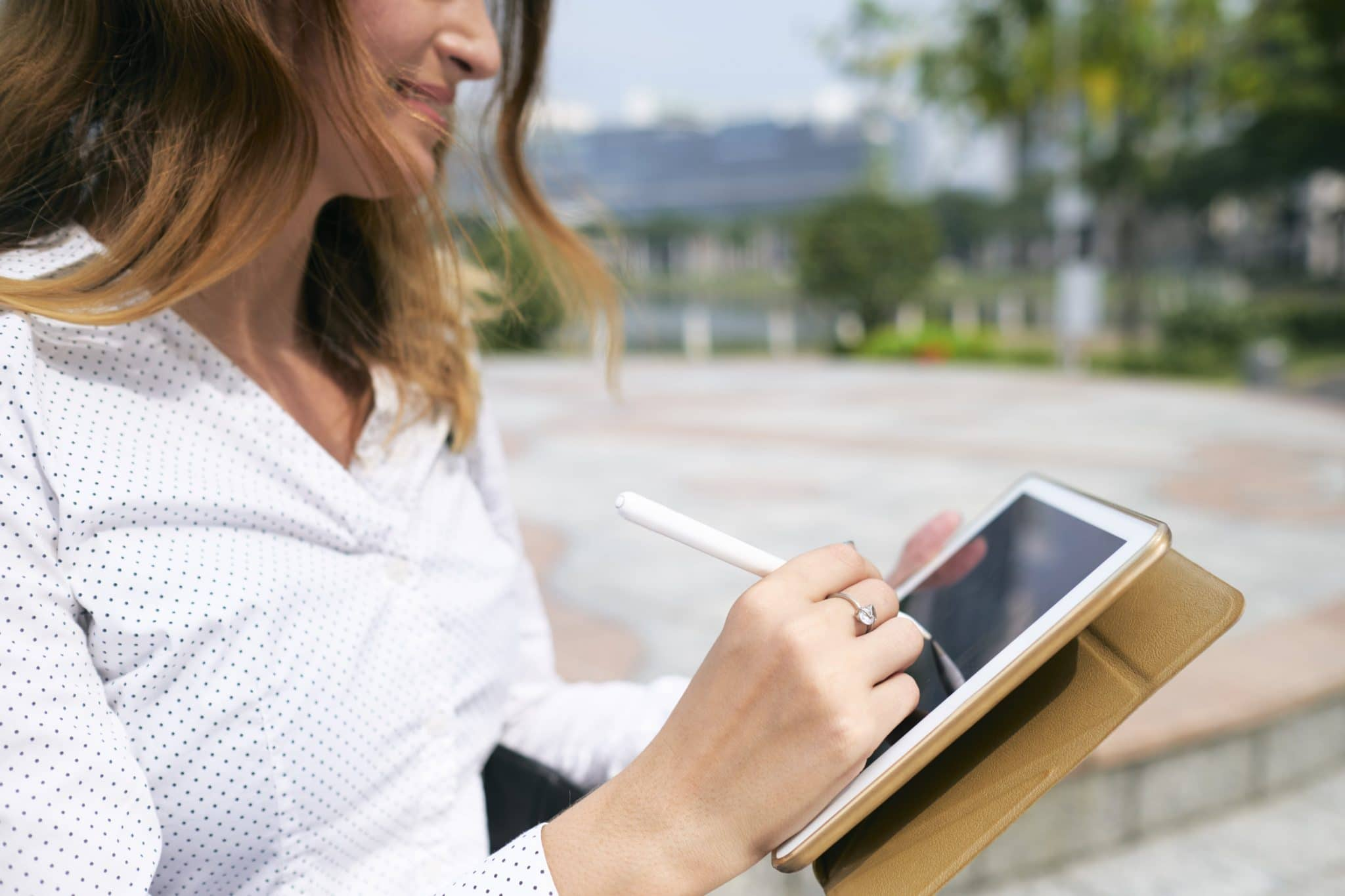 Mulher com tablet na mão fazendo assinatura eletrônica em documento