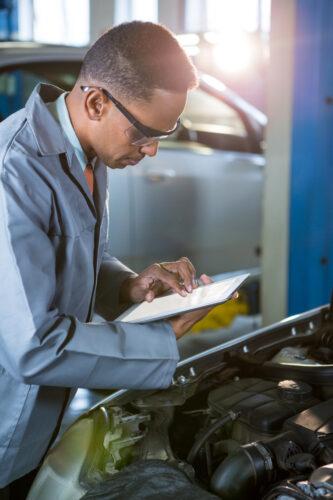Homem verificando no tablet os passos do Plano de Manutenção Preventiva do Carro.