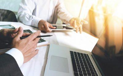 Executivos em reunião usando tablet para anotação e revisão da pauta que está sendo discutida, uma forma de se fazer automação de processos.